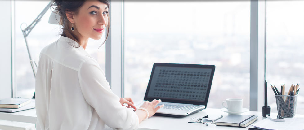 Smiling businesswoman on laptop in office